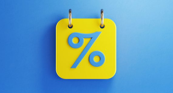 Yellow calendar with blue percentage sign on blue background. Horizontal composition with copy space. Top view.